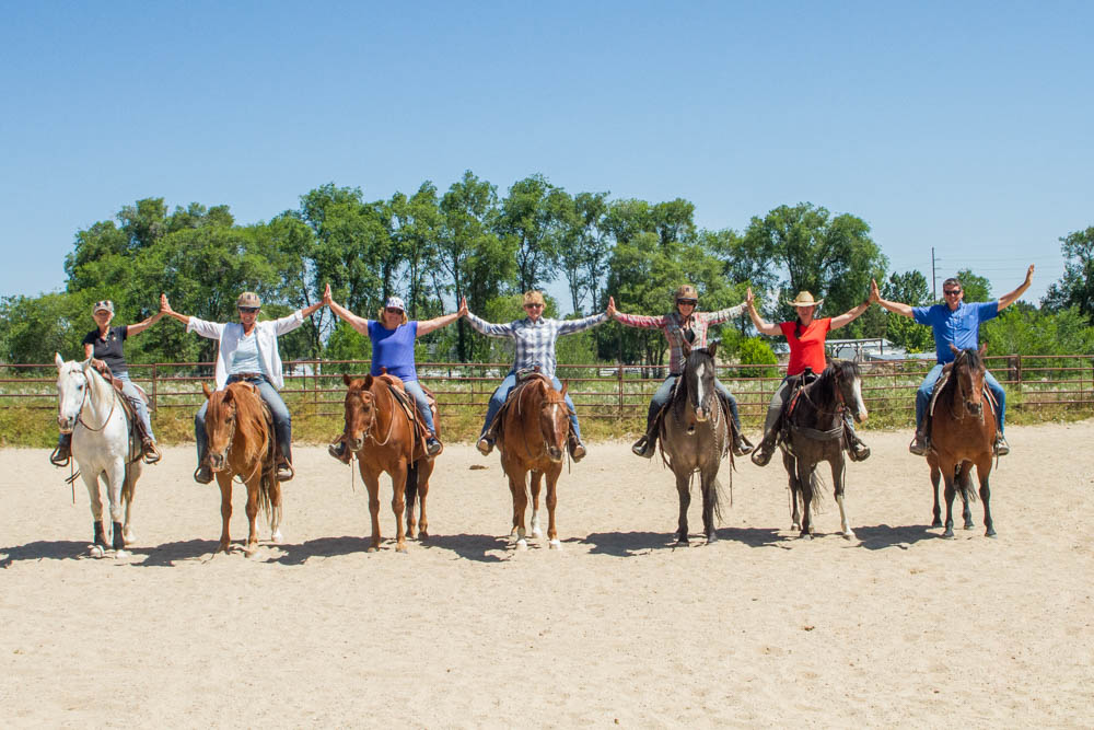 Lineup of horseback riders linking hands