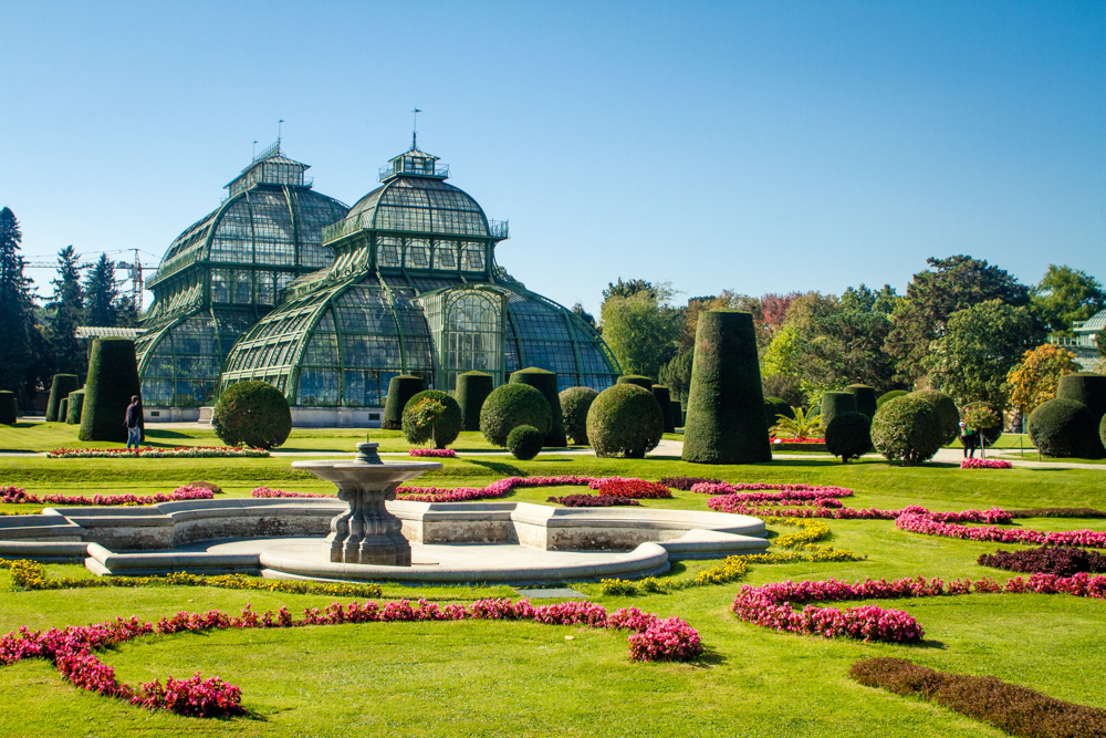 Greenhouse surrounded by ornate gardens and topiary