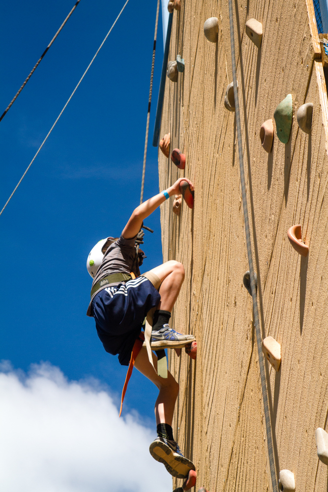 Young man scaling a climbing wall