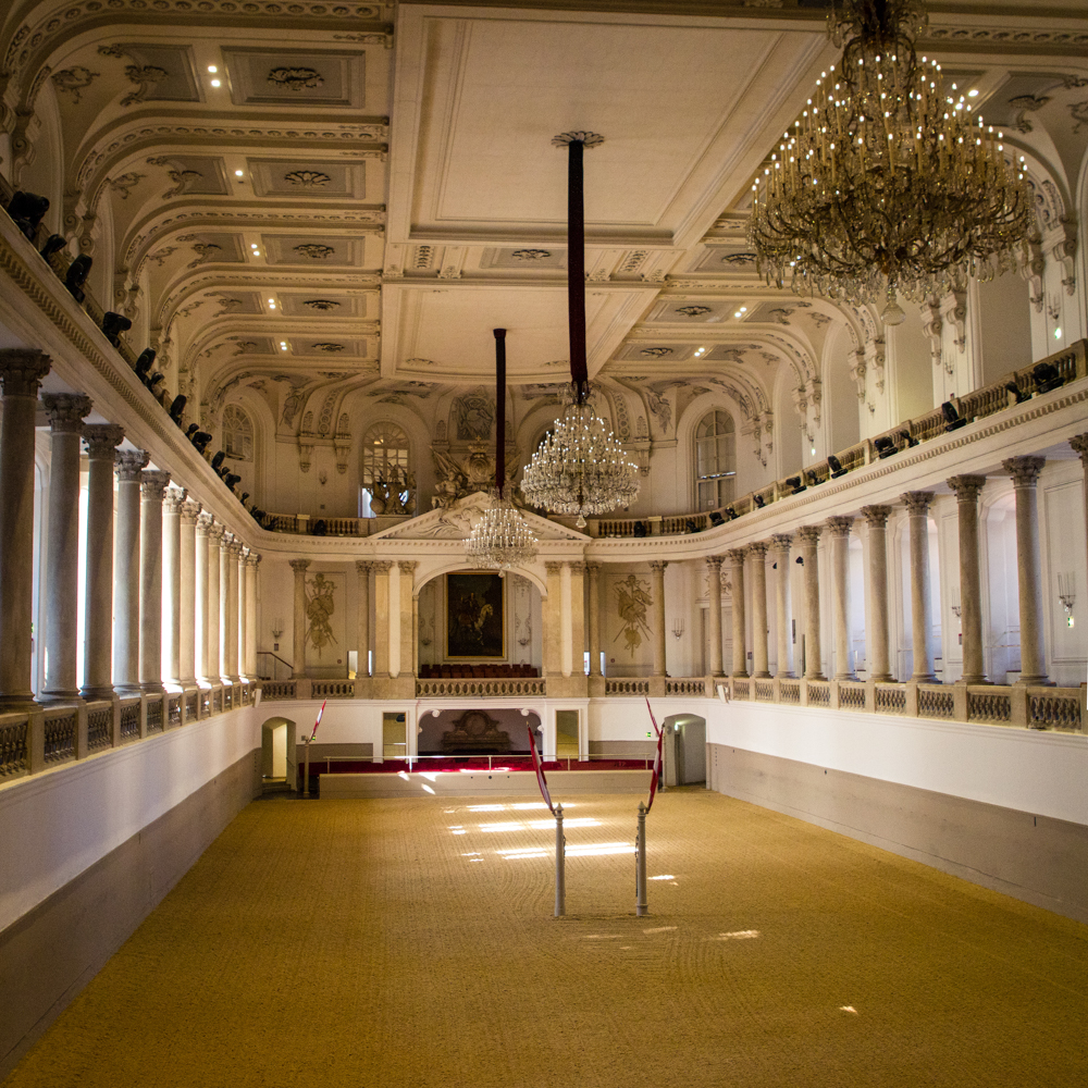 Ornate indoor horseback riding arena lined with columns and decorated with chandeliers