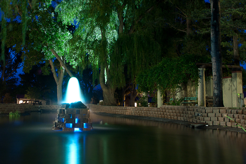Illuminated fountain in the middle of a pond