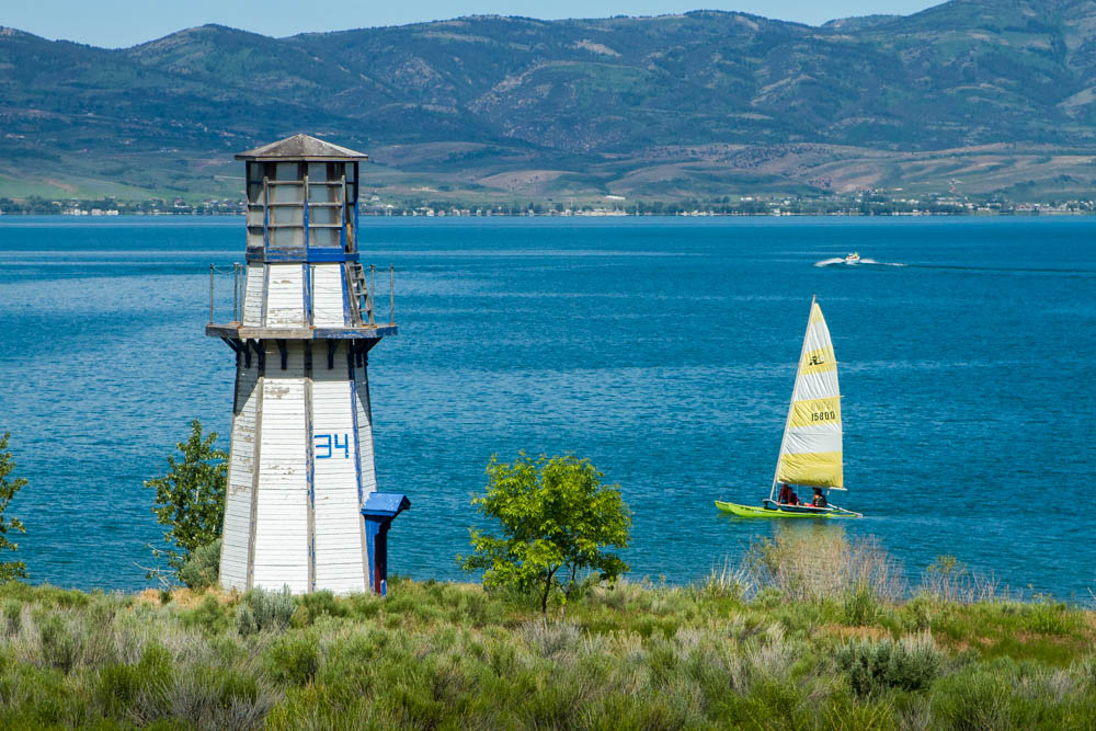 Lighthouse at the edge of a lake with a yellow sailboat in the water